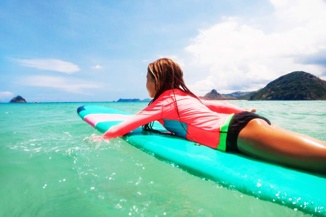 Girl padding out on surfboard